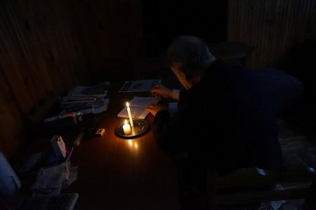 A man writes by candlelight as his neighbourhood Parque Batlle goes without electricity after a massive blackout in Argentina, in Montevideo