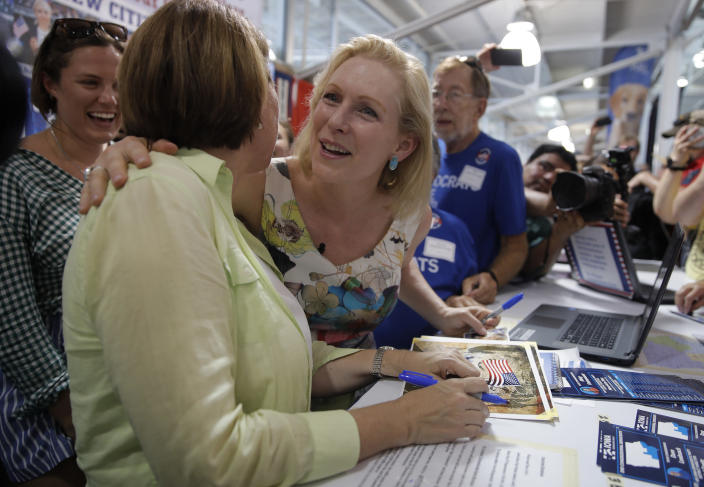 Democratic presidential candidate Sen. Kirsten Gillibrand, D-N.Y. right, embraces Democratic presidential candidate Sen. Amy Klobuchar, D-Minn., at a booth at the Iowa State Fair, Saturday, Aug. 10, 2019, in Des Moines, Iowa. (AP Photo/John Locher)