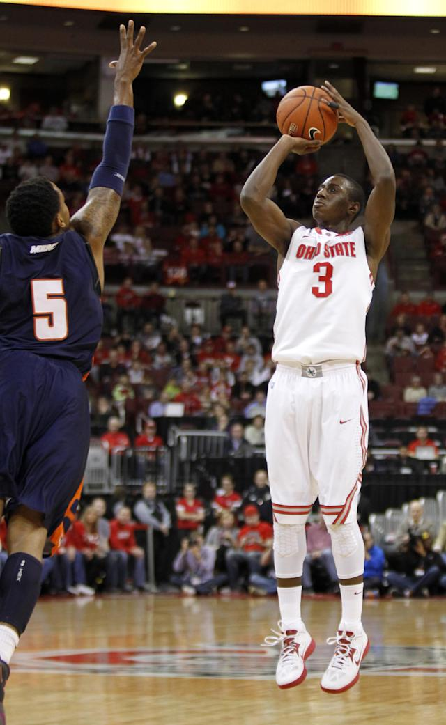 Ohio State's Shannon Scott, right, goes up for a shot against Morgan State's Justin Black during the first half of an NCAA college basketball game in Columbus, Ohio, Saturday, Nov. 9, 2013. (AP Photo/Paul Vernon)