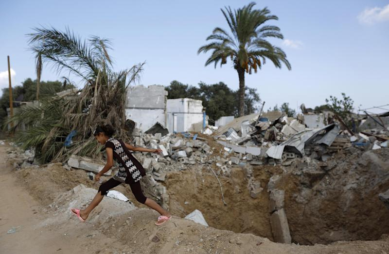 A Palestinian girl plays near her destroyed home in Bureij refugee camp on September 9, 2014 (AFP Photo/Mohammed Abed)