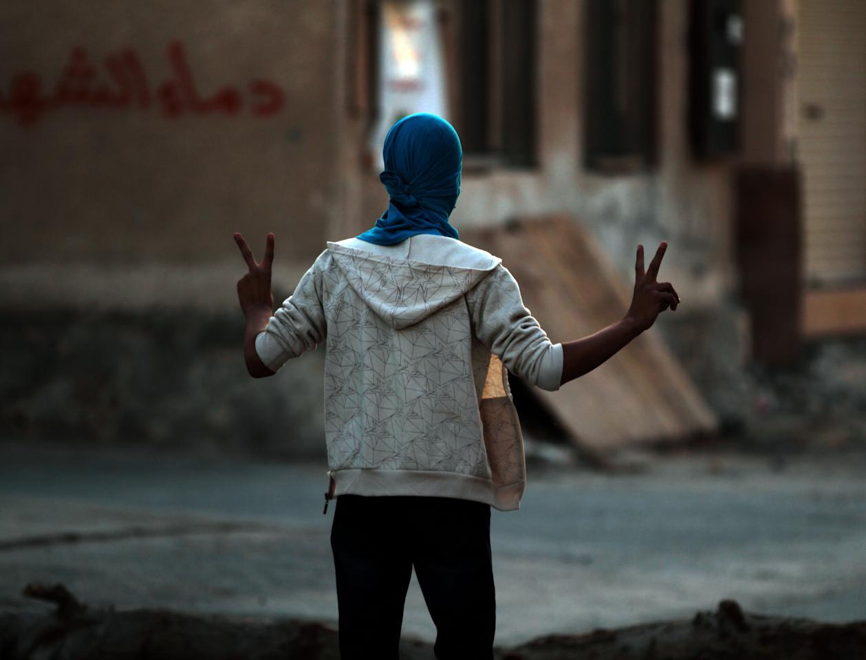 A Bahraini anti-government protester flashes the victory sign toward riot police during clashes in Abu Saiba, Bahrain, Monday, Dec. 3, 2012. (AP Photo/Hasan Jamali)