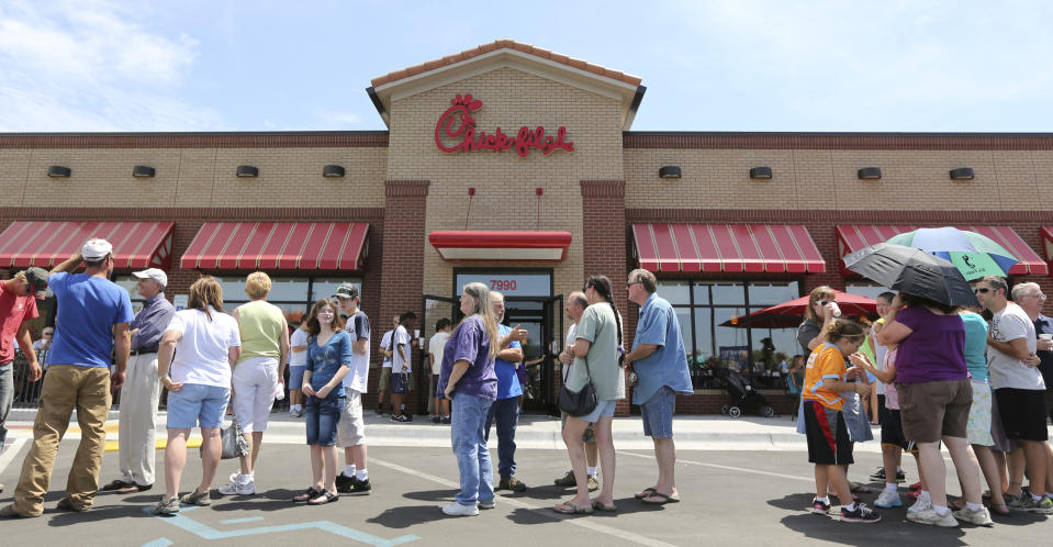"""<p> Customers stand in line for a Chick-fil-a meal at the chain's restaurant in Wichita, Kan., on Wednesday. Aug. 1, 2012. The crowd was buying meals to show their support for the company that's currently embroiled in a controversy over same-sex marriage. Former Arkansas Gov. Mike Huckabee, a Baptist minister, declared Wednesday national """"Chick-fil-A Appreciation Day."""" Opponents of the company's stance are planning """"Kiss Mor Chiks"""" for Friday, when they are encouraging people of the same sex to show up at Chick-fil-A restaurants around the country and kiss each other. (AP Photo/The Wichita Eagle, Travis Heying) </p>"""
