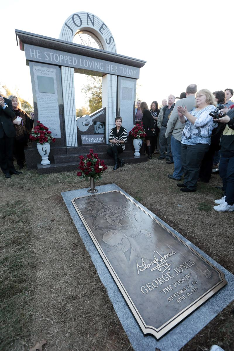 Nancy Jones, widow of country music star George Jones, listens as the Jones Boys band plays as she sits at the memorial unveiled at the late singer's grave on Monday, Nov. 18, 2013, in Nashville, Tenn. Nancy Jones spoke at the monument's dedication and announced a scholarship in her late husband's name at Middle Tennessee State University. George Jones died April 26. (AP Photo/Mark Humphrey)