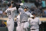 New York Yankees' Joey Gallo, center, is congratulated by Aaron Judge (99) after hitting a three-run home run against the Oakland Athletics during the third inning of a baseball game Thursday, Aug. 26, 2021, in Oakland, Calif. (AP Photo/Tony Avelar)