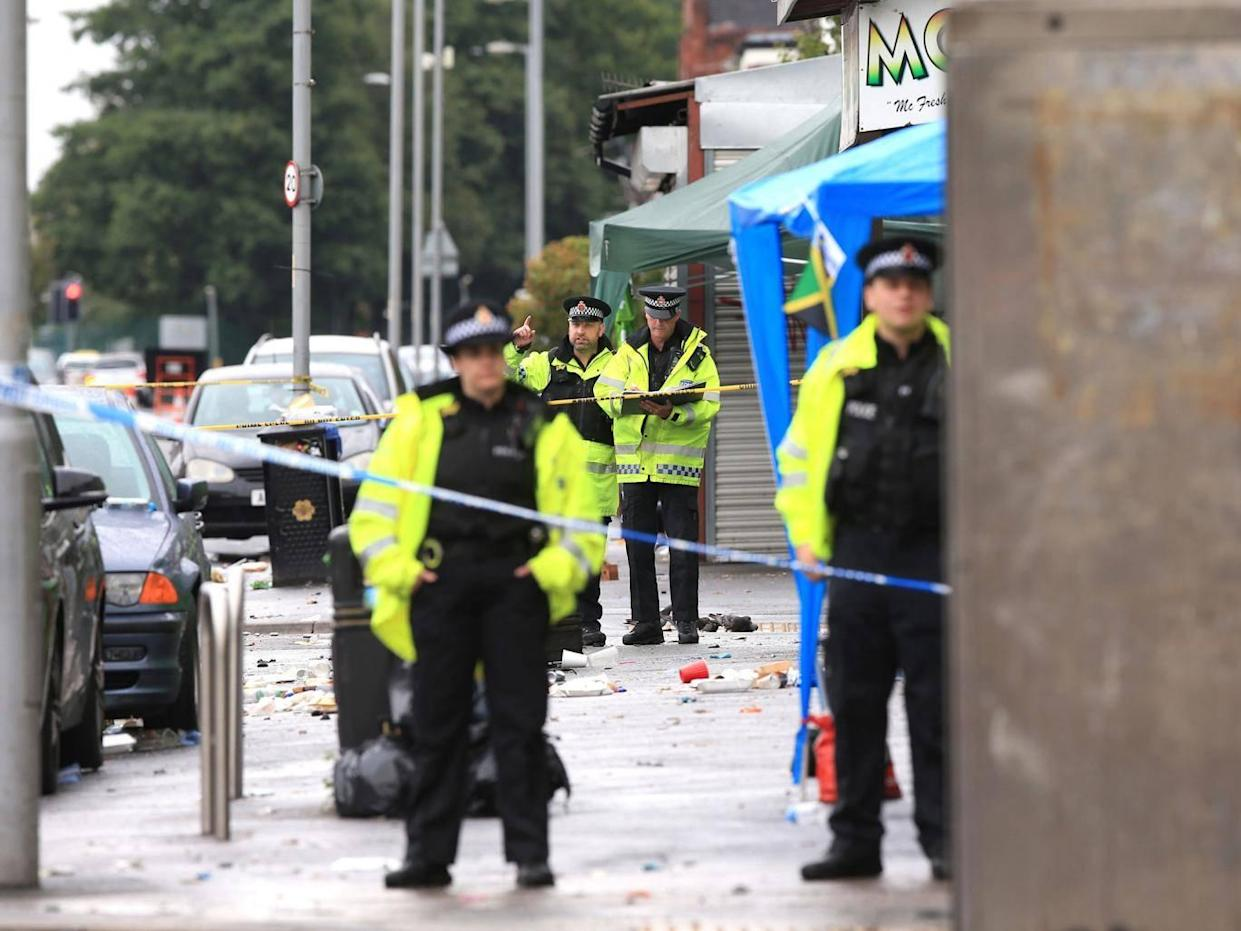 Police officers at the scene in Claremont Road, Moss Side, Manchester, where several people have been injured after a shooting (Peter Byrne/PA Wire)