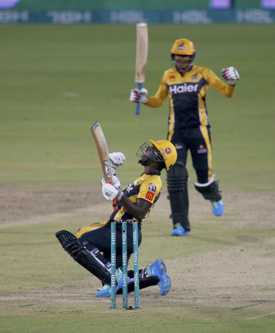 Peshawar Zalmi' Sherfane Rutherford, front, and Mujeeb Ur Rahman jublates after score level during a Pakistan Super League T20 cricket match between Quetta Gladiators and Peshawar Zalmi at the National Stadium, in Karachi, Pakistan, Friday, Feb. 26, 2021. (AP Photo/Fareed Khan)