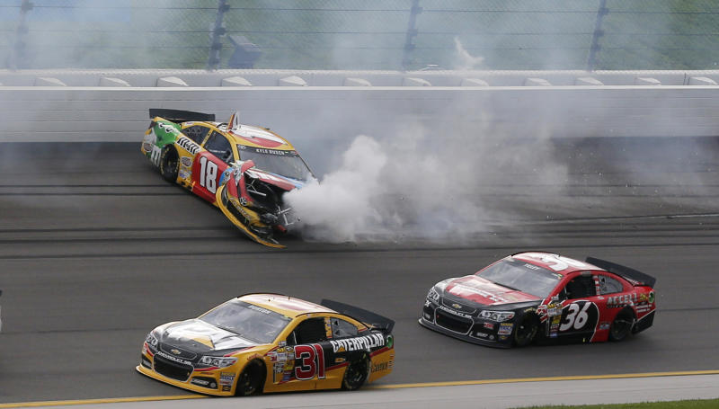 Drivers Jeff Burton (31) and J J Yeley (36) get past Kyle Busch (18) during a NASCAR Sprint Cup series auto race at Kansas Speedway in Kansas City, Kan., Sunday, Oct. 6, 2013. (AP Photo/Orlin Wagner)