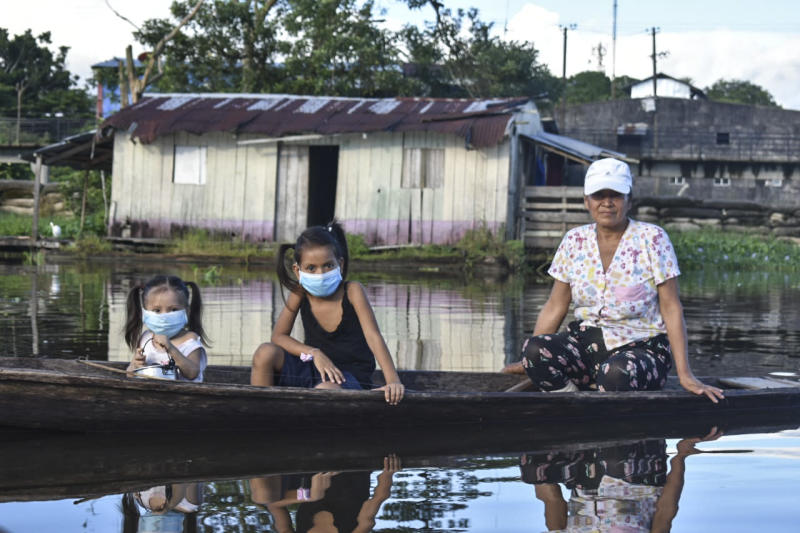 A woman and two girls wearing face masks, as a preventive measure against the spread of the novel coronavirus, COVID-19, sail at the Amazon river in Leticia, Colombia. Source: Getty Images
