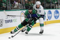 Dallas Stars center Tyler Seguin (91) and Vancouver Canucks defenseman Alexander Edler (23) compete for control of the puck in the first period of an NHL hockey game in Dallas, Tuesday, Nov. 19, 2019. (AP Photo/Tony Gutierrez)