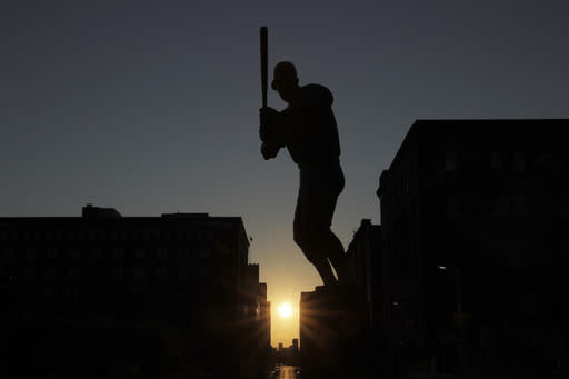 The sun sets in the distance as a statue of St. Louis Cardinals great Stan Musial stands outside a quiet Busch Stadium Friday, Aug. 7, 2020, in St. Louis. Major League Baseball announced Friday that a three-game series between the Chicago Cubs and Cardinals set for this weekend in St. Louis has been postponed after two more Cardinals players and a staff member tested positive for the coronavirus. (AP Photo/Jeff Roberson)