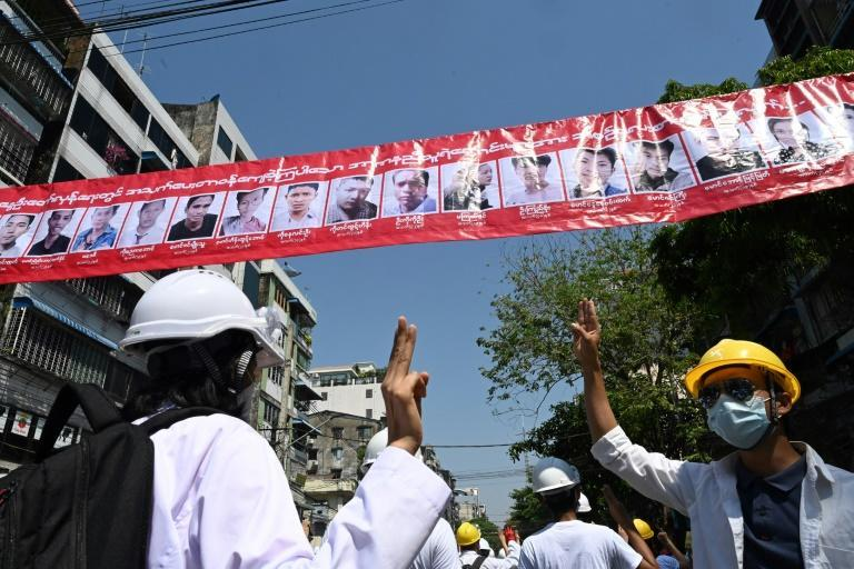 Medical personnel and students in Myanmar hold up the three-finger salute below a row of portraits of people who have died since the military coup
