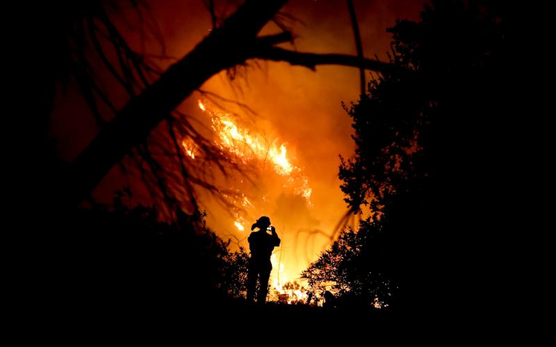 A firefighter tackles a wildfire in Montecito, California - AP