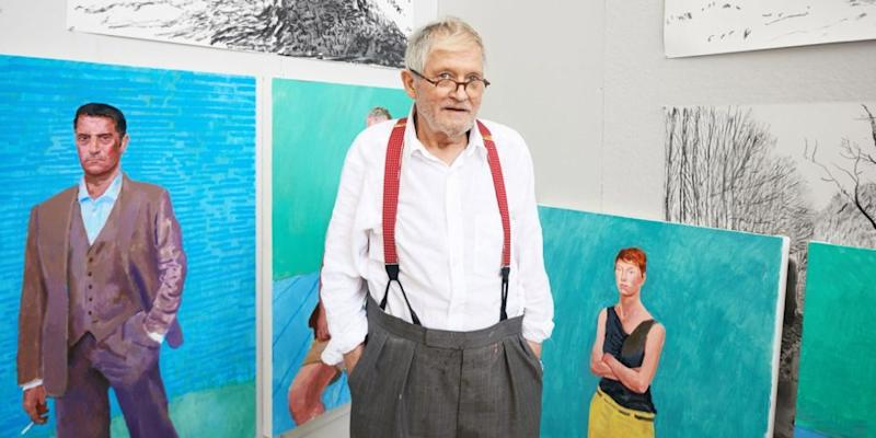 David Hockney standing in front of his paintings