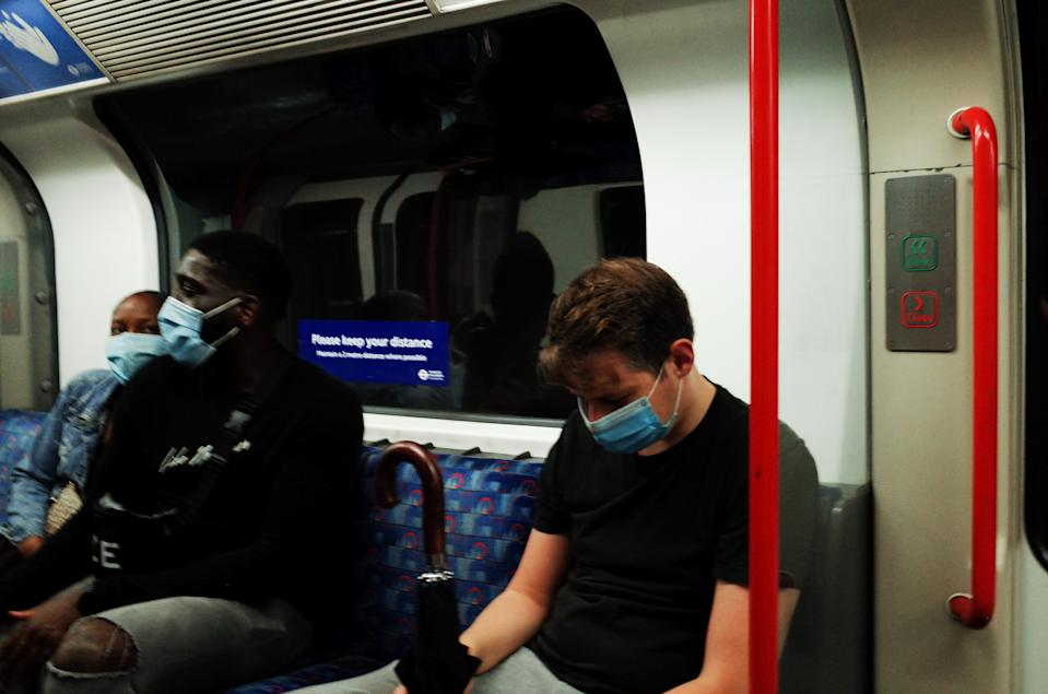 Passengers wearing face masks, currently mandated on public transport, ride a Central line tube service in London, England, on August 14, 2020. Passenger numbers on the London Underground remain well below pre-pandemic levels as the city continues its hesitant emergence from the coronavirus lockdown, with covid-19 fears still keeping many from using public transport. (Photo by David Cliff/NurPhoto via Getty Images)