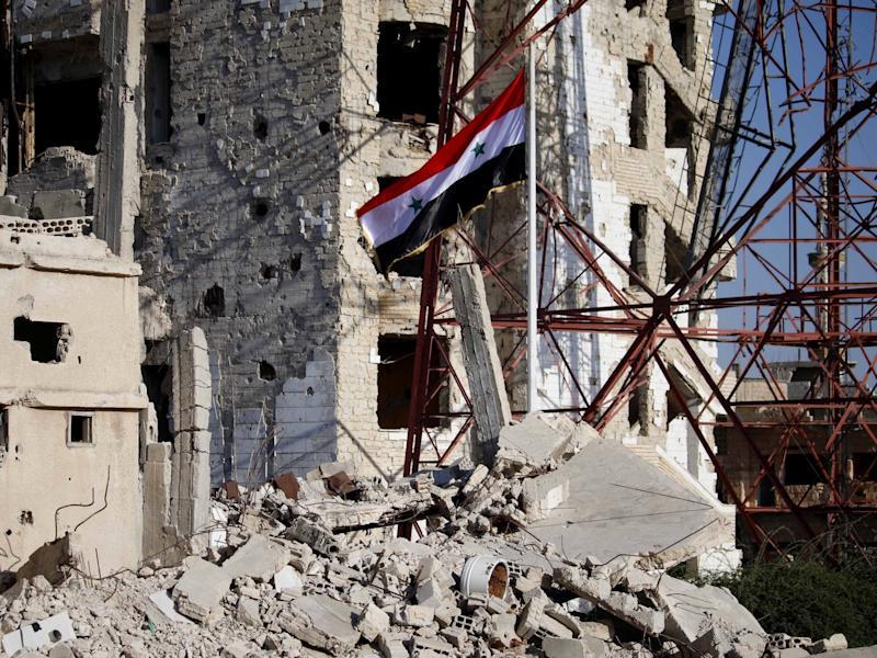 The Syrian national flag rises in the midst of damaged buildings in Deraa: AFP