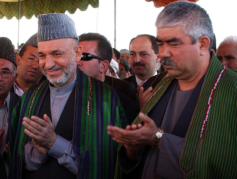 FILE - In this Sunday, Sept. 26, 2004 file photo, Afghan President Hamid Karzai, left, accompanied by the presidential candidate and regional commander General Abdul Rashid Dostum applaud during his visit to Shiberghan, about 400 kilometers (250 miles) northwest of the capital Kabul. Secret contacts are again reported to be underway for an Afghanistan peace deal, but neither analysts nor the belligerents see hope they will succeed. Many wonder whether Karzai even wants a peace deal before the April election. He is ineligible for a third term, and stalling until he is out of office would punt the tough decisions to his successor. And the Taliban still needs to prove it can be trusted not to exact revenge for alleged atrocities by Afghan leaders. The ill-feeling resonates in the case of Rashid Dostum, an Uzbek warlord who the Taliban, as well as Western human rights organizations, accuses of killing thousands of surrendering Taliban during the U.S.-led 2001 invasion. Dostum is running for vice president in the election.(AP Photo/Emilio Morenatti, File)