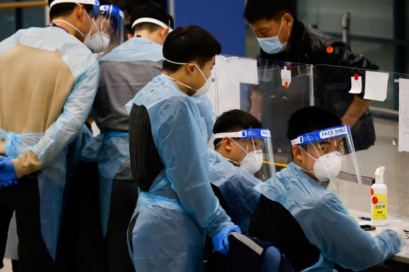 Workers wearing protective gear check a passenger from overseas as he arrives at the Incheon International Airport, in Incheon