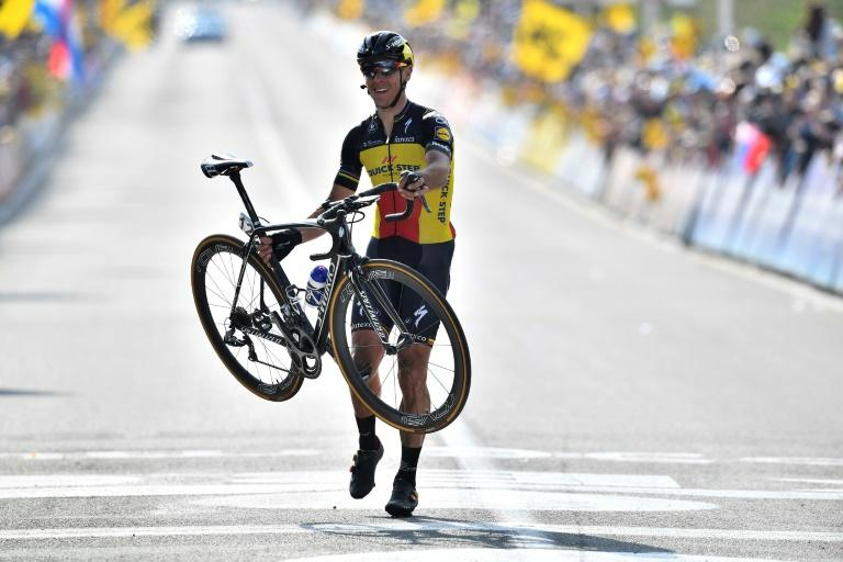 Belgian cyclist Philippe Gilbert carries his bike as he crosses the finish line to win the Tour of Flanders, a 260km race from Antwerp to Oudenaarde, on April 2, 2017