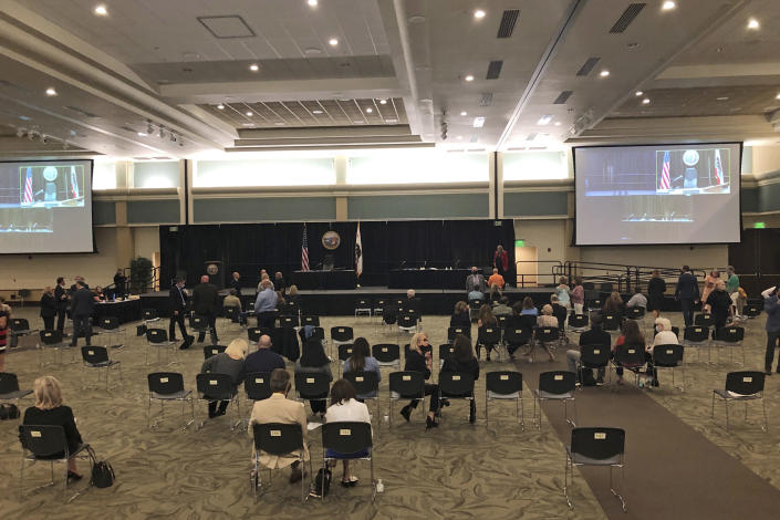 People gather in a courtroom set up in a ballroom where a 74-year-old former police officer is tentatively set to plead guilty Monday, June 29, 2020, to being the elusive Golden State Killer in Sacramento, Calif. The hearing comes 40 years after a sadistic suburban rapist terrorized California in what investigators only later realized were a series of linked assaults and slayings. The plea deal will spare Joseph DeAngelo any chance of the death penalty, but in partial return survivors of the assaults that spanned the 1970s and 1980s expect him to admit to dozens of rapes that could not be criminally charged because too much time has elapsed. (AP Photo/Rich Pedroncelli)