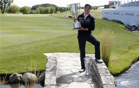 Zach Johnson of the U.S. poses with the trophy after winning the BMW Championship golf tournament at the Conway Farms Golf Club in Lake Forest, Illinois, September 16, 2013. REUTERS/Jim Young