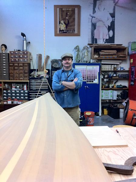 "In this February 2012 image released by Jessica Glazer, Nick Offerman, who plays Ron Swanson on NBC's ""Parks & Recreation,"" stands next to one of two canoes he built as shown in his Woodworking Studio in Los Angeles. Building boats requires a particular kind of commitment. It's complex and expensive. It can take months or years. And it can be addictive, working out in the garage, sawdust clinging to your clothes, making mistakes and finding the solutions yourself. (AP Photo/Jessica Glazer)"