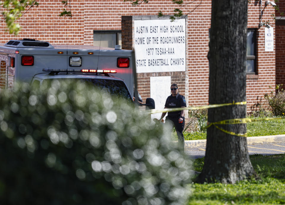A member of the Knoxville police forensics team works the scene of a shooting at Austin-East Magnet High School in Knoxville, Tenn., Monday, April 12, 2021. (AP Photo/Wade Payne)