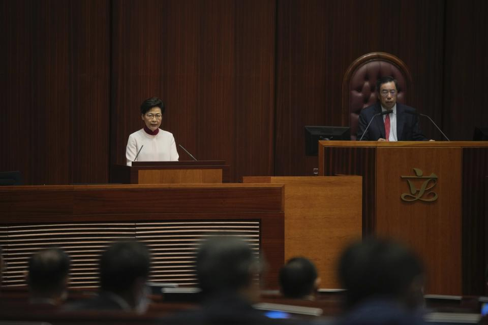 Hong Kong Chief Executive Carrie Lam, left, delivers her policies at the chamber of Legislative Council in Hong Kong, Wednesday, Oct. 6, 2021. Lam announced a major development plan Wednesday for Hong Kong's border area with mainland China in the last annual policy address of her current term. (AP Photo/Kin Cheung)
