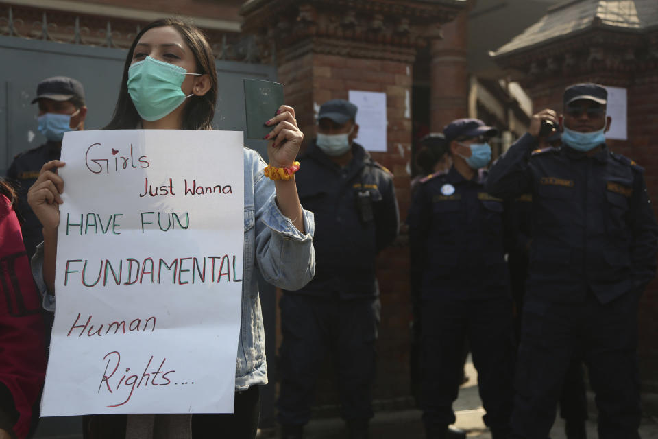 A Nepalese woman holds a placard against a proposed rule which restricts foreign travel for women under 40 years during a protest outside the Department of Immigration in Kathmandu, Nepal, Thursday, Feb.11, 2021. Nepal government is proposing a new rule that says women under 40 years of age must seek consent from the family–and even the concerned ward office–to travel abroad on a visit visa. (AP Photo/Niranjan Shrestha)