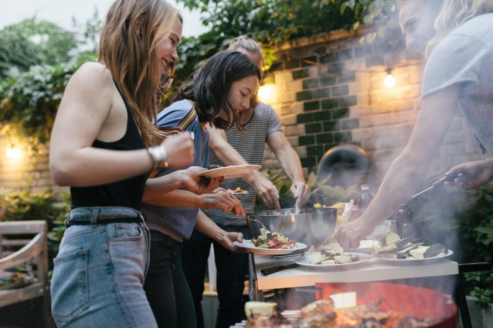 A young group of friends are helping themselves to freshly prepared food at a summer evening Barbecue.