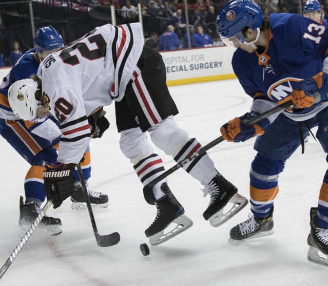 New York Islanders center Mathew Barzal (13) trips Chicago Blackhawks left wing Brandon Saad (20) during the first period of an NHL hockey game, Saturday, March 24, 2018, in New York. (AP Photo/Mary Altaffer)