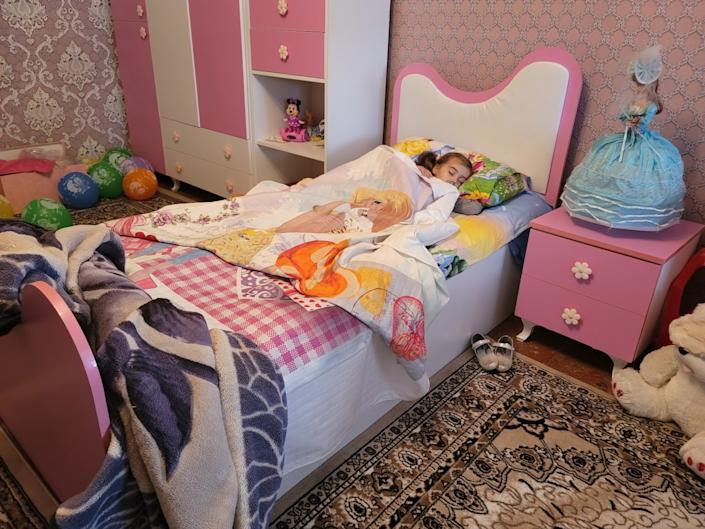 Three-year-old Khadija, who lost her parents and sister in a missile strike on Ganja, Azerbaijan, lies in her bed.
