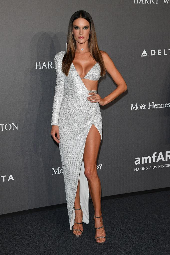 <p>The recently retired Victoria's Secret Angel is no stranger to wearing a bra in public, but this metallic dress with a revealing bra attachment definitely takes the cake. (Photo: Getty Images) </p>