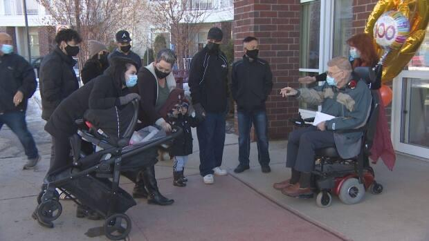 Charlie Cox celebrated his 100th birthday with family and friends outside his College Park residence in Regina on Sunday. (CBC News - image credit)