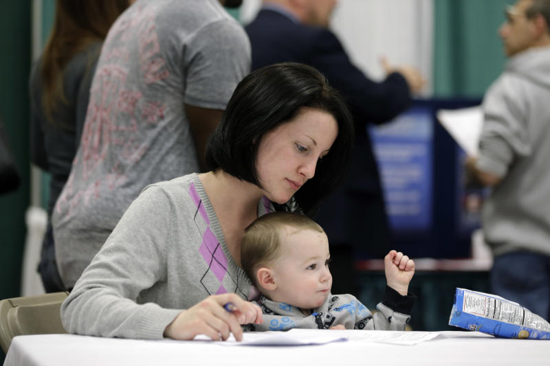 In this April 22, 2014 photo, Sarah Keegan of Windham, N.Y., with her son Kevin, fills out paperwork during a job fair at Columbia-Greene Community College in Hudson, N.Y. The Labor Department on Friday, May 2, 2014 said U.S. employers added a robust 288,000 jobs in April, the most in two years, the strongest evidence to date that the economy is picking up after a brutal winter slowed growth. (AP Photo/Mike Groll)