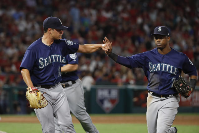 Seattle Mariners starting pitcher Marco Gonzales, left, greets Jean Segura with a fist bump as they walk off the field after the sixth inning of a baseball game against the Los Angeles Angels, Wednesday, July 11, 2018, in Anaheim, Calif. (AP Photo/Jae C. Hong)