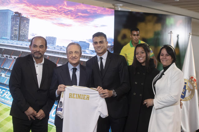 Brazilian player Rainier, centre, holds up his new shirt next to club president Florentino Perez, 2nd left and family members during his official presentation after signing for Real Madrid at the Santiago Bernabeu stadium in Madrid, Spain, Tuesday, Feb. 18, 2020. (AP Photo/Paul White)