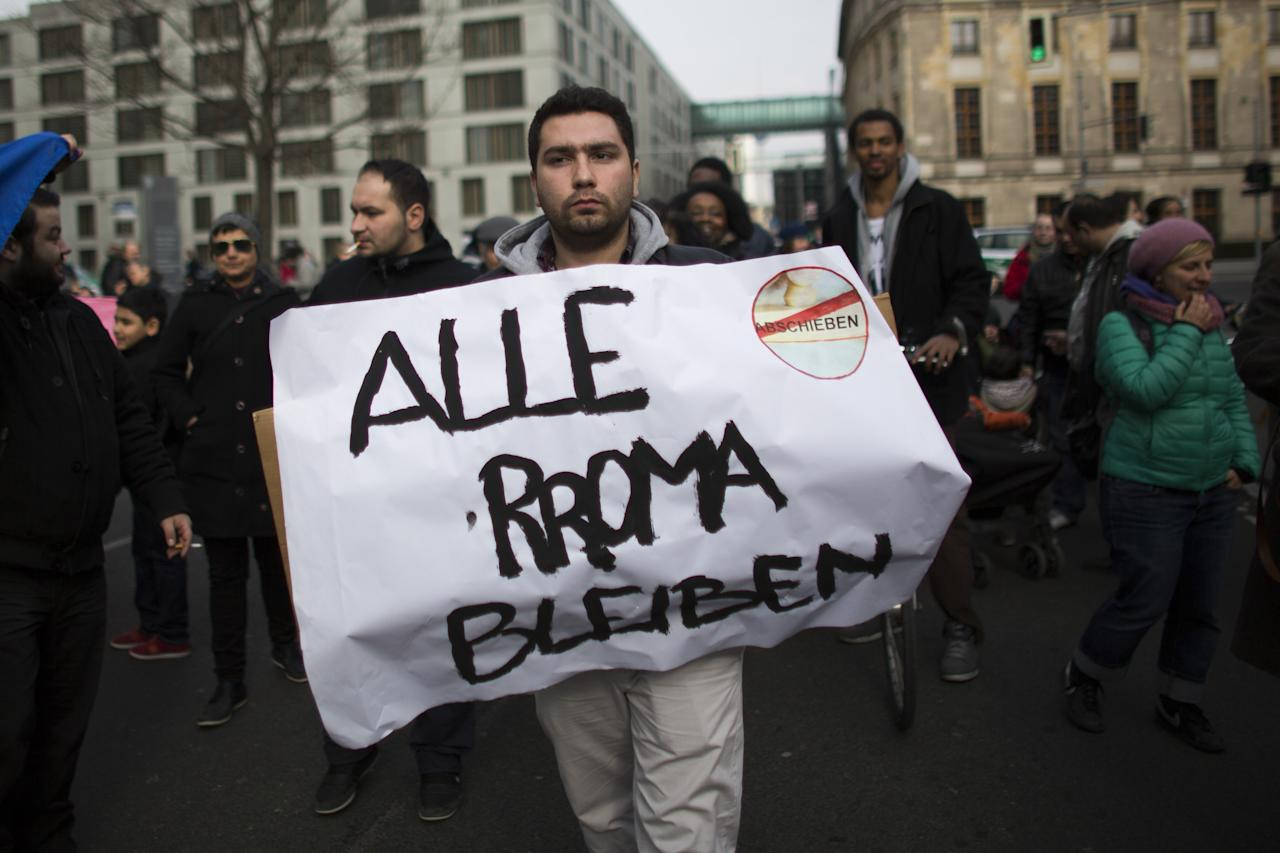 "BERLIN, GERMANY - APRIL 08:  A man holds a banner with the written slogan ""Alle Roma Bleiben"" (All Roma Stay) as ethnic Roma protest against discrimination against Roma on International Roma Day on April 8, 2013 in Berlin, Germany. Western Europe has experienced a large influx of Roma, who are also called Gypsies, from Romania and Bulgaria in recent years following the accession of the two countries to the European Union. Restrictions on the rights of Romanian and Bulgarian citizens to work in the EU are scheduled to end at the end of 2013.  (Photo by Carsten Koall/Getty Images)"