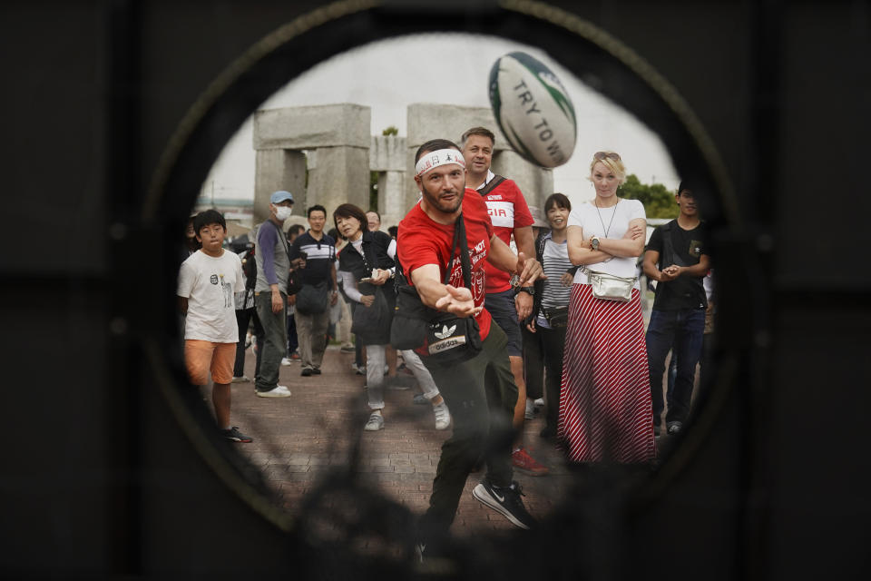 Fans play a game outside Hanazono Stadium before the Rugby World Cup Pool D game between Georgia and Fiji in Osaka, Japan, Thursday, Oct. 3, 2019. (AP Photo/Jae C. Hong)