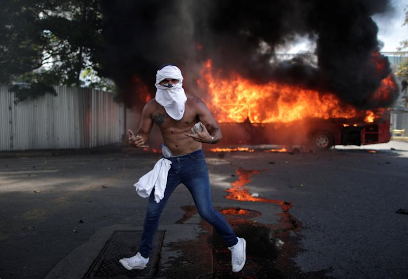 "An opposition demonstrator gestures in front of a burning bus, while holding a rock, near the Generalisimo Francisco de Miranda Airbase ""La Carlota"" in Caracas, Venezuela April 30, 2019. (Photo: Ueslei Marcelino/Reuters)"