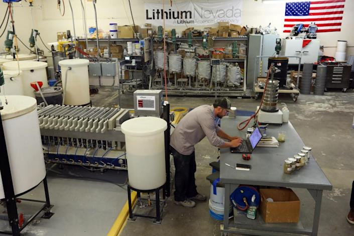 A technician at Lithium Americas bends over a laptop amid equipment in a large lab.