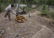 Yasir Lal, a Christian lays a wreath on the grave of his Nadeem Jordon who was killed by gunmen because he rented in a Muslim neighborhood, at a cemetery in Peshawar, Pakistan, Thursday, July 9, 2020. Analysts and activists say minorities in Pakistan are increasingly vulnerable to Islamic extremists as Prime Minister Imran Khan vacillates between trying to forge a pluralistic nation and his conservative Islamic beliefs. (AP Photo/Muhammad Sajjad)
