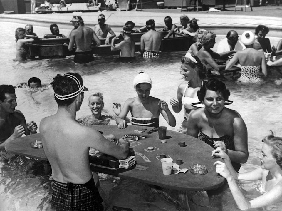 <p>Customers gamble at a Las Vegas casino pool in 1957. Gambling wasn't the only attraction during this decade, as some of the biggest stars of film and music performed and brought entertainment to the city. </p>