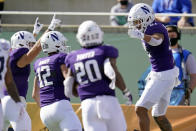 Northwestern wide receiver Ramaud Chiaokhiao-Bowman, right, celebrates his 35-yard touchdown catch against Auburn with teammates including quarterback Peyton Ramsey (12), and running back Cam Porter (20) during the first half of the Citrus Bowl NCAA college football game, Friday, Jan. 1, 2021, in Orlando, Fla. (AP Photo/John Raoux)