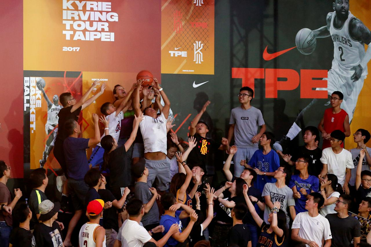 Fans jump for a ball throwing by NBA player Kyrie Irving of the Cleveland Cavaliers during a promotional event in Taipei, Taiwan July 22, 2017. REUTERS/Tyrone Siu