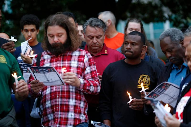 People hold candles during a candlelight vigil outside city hall for deceased and injured workers from the Hard Rock Hotel construction collapse.