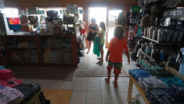 PHOTO: Tara Clark and her children, Eli, 9, and Lucy, 11, shop at Ocracoke Outfitters in Hatteras, N.C., July, 28, 2017. (Ethan Hyman/The News & Observer via AP)