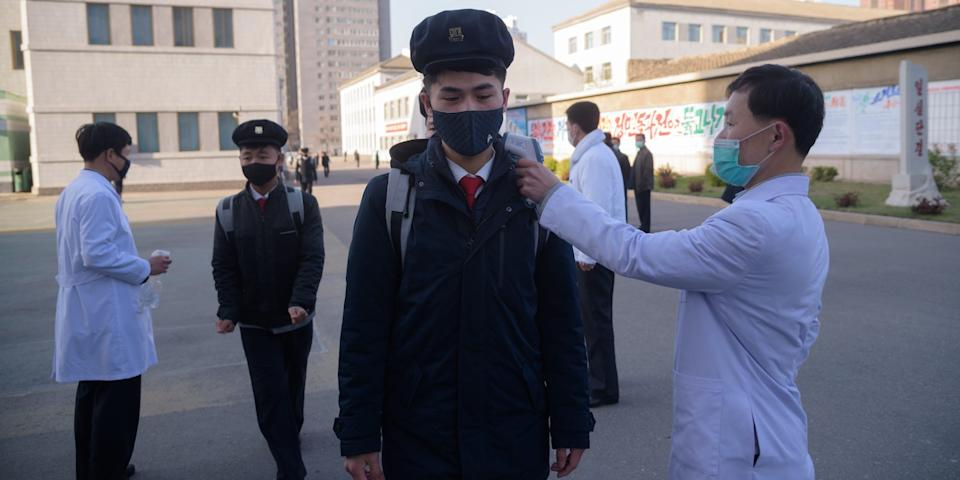 "Students wearing face masks disinfect their hands and undergo a temperature check as they arrive for a lecture on preventative measures against the COVID-19 novel coronavirus at the Pyongyang University of Medicine in Pyongyang on April 22, 2020. <p class=""copyright"">Kim Won Jin/AFP via Getty Images</p>"