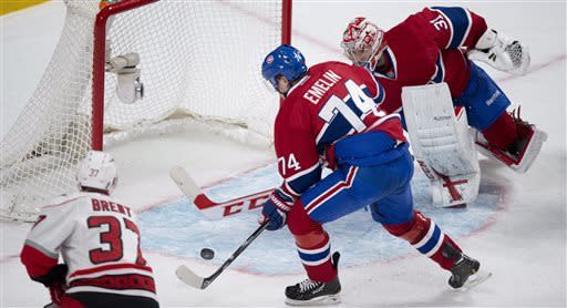Montreal Canadiens goalie Carey Price and defenseman Alexei Emelin avoid giving a rebound to Carolina Hurricanes' Tim Brent during second period NHL hockey action Monday, April 1, 2013 in Montreal. T (AP Photo/ The Canadian Press, Paul Chiasson)