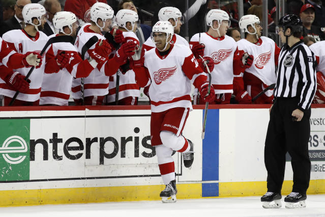 Detroit Red Wings left wing Andreas Athanasiou (72) greets teammates after scoring a goal against the New Jersey Devils during the second period of an NHL hockey game, Thursday, Feb. 13, 2020, in Newark, N.J. (AP Photo/Kathy Willens)