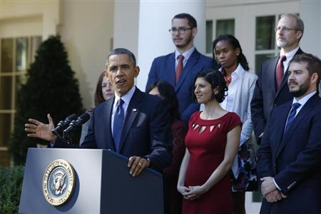 U.S. President Obama stands with Affordable Care act registrants and beneficiaries as he speaks about healthcare at the White House in Washington